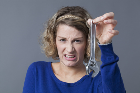 manual work: female DIY concept - scared young blond woman having aversion at holding wrench as symbol of manual work and mechanics handiwork Stock Photo