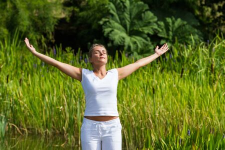 inner beauty: outdoors meditation - gorgeous young yoga woman outstretching arms,closing eyes to focus on inner beauty to relax and meditate with green bushy background and summer daylight