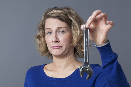 manual work: female DIY concept - scared young blond woman having disgust at holding spanner as symbol of manual work and mechanics handiwork