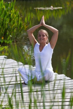 inner peace: outdoors meditation - happy young yoga woman exercising in praying pose,closing eyes to focus on inner peace to relax and meditate with green and water background, summer daylight