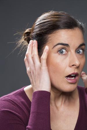 desilusion: sorpresa y decepción concepto - retrato de una mujer de 30 años morena con las manos en las primeras arrugas que cuestionan su rostro de piel, tiro del estudio, fondo negro Foto de archivo
