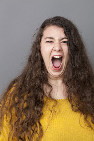 20's: stressed out overweight 20s woman with long brown hair screaming loud for expressing rage and anger