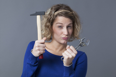 playfulness: female DIY concept - cheerful young blond woman holding wrench and hammer with playfulness for manual expertise Stock Photo