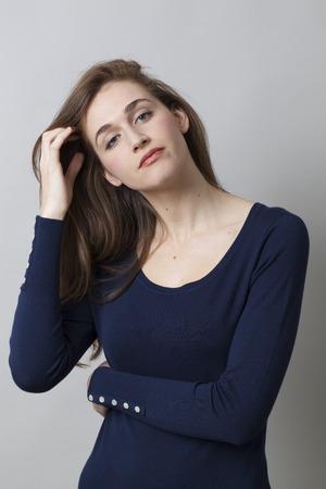 desilusion: concepto decepción - triste mujer joven con el pelo marrón largo de pensar y expresar arrepentimiento o renuncia con la mano y la cabeza gesto