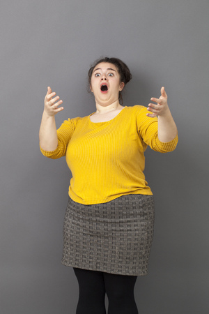 implore: stunned xxl 30s woman with extrovert outfit acting surprised with a theatrical expression and moving her torso backwards Stock Photo