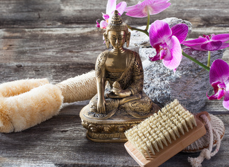 inner beauty: spa beauty treatment concept - symbol of washing-up and exfoliation for inner beauty with Buddha on old wood, gray texture stones and pink orchid flower background for authentic retreat decor Stock Photo