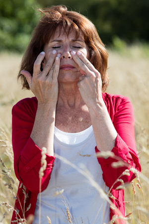 aging face: Hay fever allergies - beautiful aging woman with sinus pain massaging her face for soothing headache in dry meadow,natural summer daylight Stock Photo
