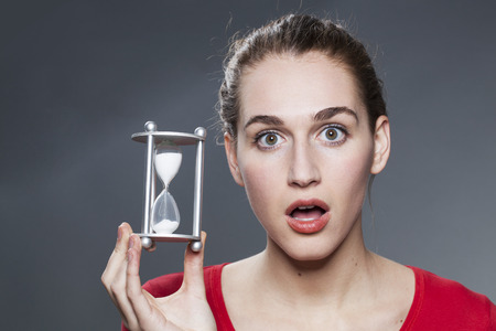 mesmerized: stunned beautiful young woman holding hourglass for concept of time management