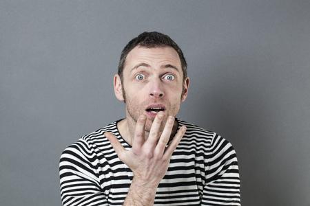 decepci�n: sorpresa y decepci�n concepto - retrato de un hombre de 40 a�os sorprendi� con la mano en el primer plano de la incomprensi�n y confusi�n gesto, tiro del estudio Foto de archivo