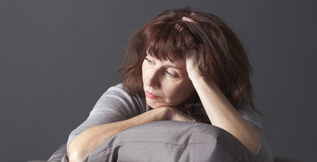 tired mature woman resting her face and hands laying down on cushions for comfort while having health care problems Archivio Fotografico