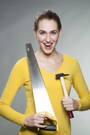 prove: female DIY concept - thrilled beautiful young woman holding saw and hammer to prove her home handiwork expertise Stock Photo