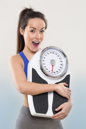 loose weight: laughing young woman training herself to loose weight Stock Photo