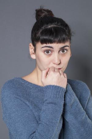 decepci�n: sorpresa y decepci�n concepto - retrato de una mujer de 20 a�os morena llorando con los ojos y las manos juntas confusas, tiro del estudio