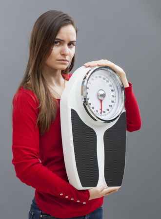 weight control: frustrated young woman with weighting scale in hands for concept of weight loss or weight control Stock Photo