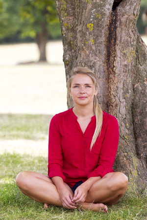 suntanned: wellbeing & tree concept - smiling young suntanned blond woman sitting under a tree with legs crossed enjoying free time,staring at camera,natural summer daylight