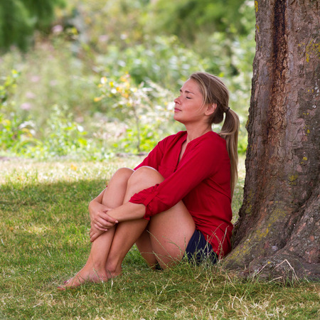 wellbeing & tree concept - happy young blond woman sitting under a tree with legs crossed,closing eyes enjoying free time,natural summer daylight