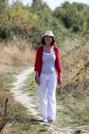 wandering: wellbeing in countryside - beautiful mature woman with summer hat wandering alone and smiling with field flower in mouth,natural summer daylight