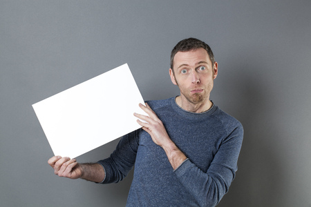 stunned: stunned 40s man looking surprised in holding a stressful news on a blank white board