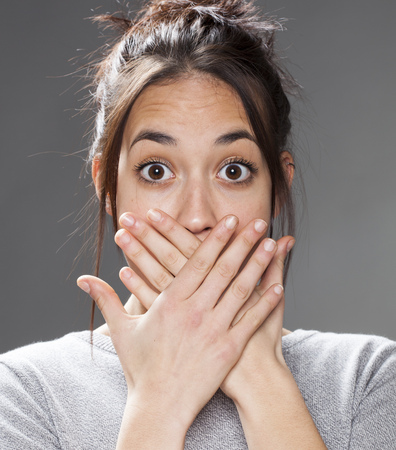 sorpresa: sorpresa y decepci�n concepto - retrato de una mujer multirracial joven poniendo sus manos en la boca de discreci�n, tab� o el silencio, tiro del estudio
