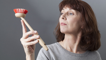 beautiful mature woman contemplating dish brush as an obsessive cleaning housewife Фото со стока