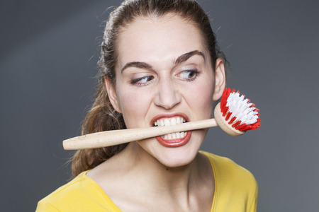 rebellion: young gorgeous woman biting dish brush for housework rebellion and cleaning stress