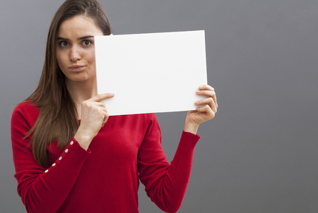 unhappy young woman frowning at a questioning information held on a blank banner