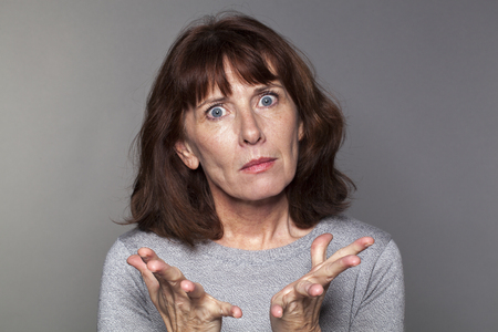 50s: portrait of exasperated 50s woman losing faith with palm hands opened for anger Stock Photo