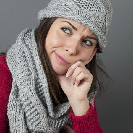 coldness: disappointment concept - unhappy young brunette with winter hat and scarf frowning in thinking about comfortable temperature or coldness Stock Photo