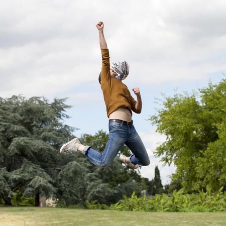 extrovert: celebrating success outdoors concept - dynamic modern man jumping with arms raised up to the sky with strength for ambition and happiness in green park,natural summer daylight