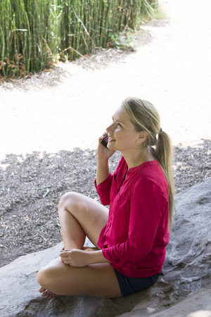 20's: outdoors communications - thrilled suntanned 20s woman sitting with crossed legs talking about her vacation on the phone,natural summer daylight Stock Photo