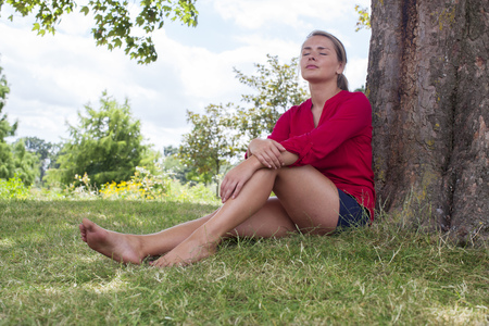 bare feet girl: wellbeing & tree concept - beautiful young suntanned blond woman resting under a tree,closing eyes for relaxation,natural summer daylight,low angle Stock Photo