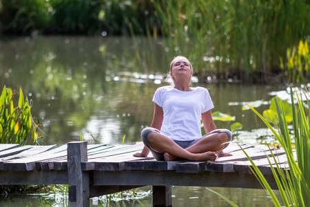 relajación al aire libre - hermosa mujer joven disfrutar de yoga para relajarse en un puente de madera con el primer plano verde y el fondo del agua, verano exótico luz del día