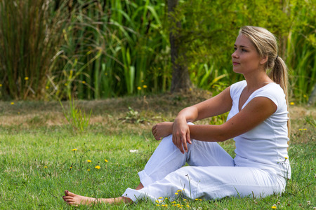 bare feet: relaxation outdoors - thinking young woman resting on grass with bare feet with green surrounding, profile view, summer daylight