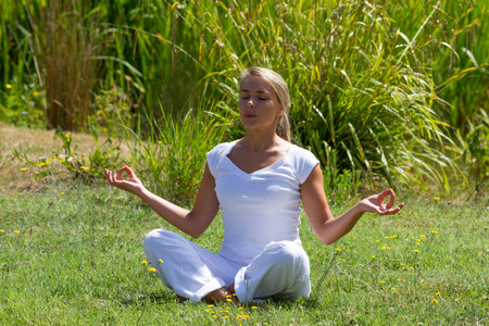 inner peace: outdoors meditation - young yoga woman exercising in lotus pose,closing eyes to focus on inner peace to relax and meditate on grass with green bushy background Stock Photo