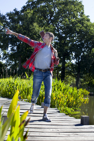 green environment: casual music outdoors - cool male musician holding guitar on shoulder walking on wooden bridge for rehearsal in city park