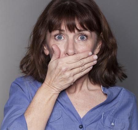 belle brune: concept de la peur - s�duisante femme m�re cachant sa bouche avec sa main d'un air surpris et stress� avec les yeux grands ouverts, gros plan dans tourn� en studio