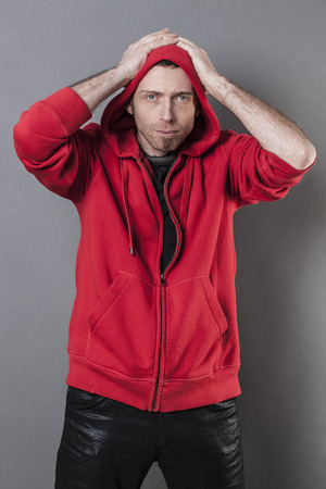 resignation: disappointment concept - speechless middle age man with hoodie on with both hands on his head expressing unhappy resignation or upsetting mistake Stock Photo
