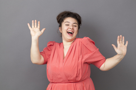 success concept - extrovert young fat girl dancing wearing a vintage dress with both hands raised expressing her achievement and happiness Stock Photo - 47013718