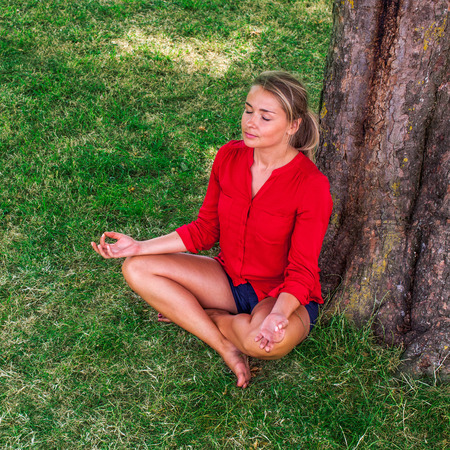 escaping: outdoors meditation - summer young yoga woman escaping in closing eyes,relaxing in sitting in lotus pose next to a tree, summer daylight Stock Photo