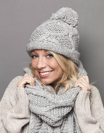 trendy warm winter - beautiful young blond woman wrapped up in gray wool winter hat and scarf smiling for comfort and cozy temperature
