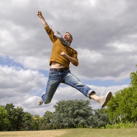 hombres jovenes: celebrando el éxito al aire libre concepto - el hombre moderno divertido saltando con los brazos levantados con la energía para la victoria y la felicidad en parque verde, la luz del día verano naturales Foto de archivo