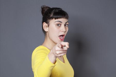 firmeza: mujer joven morena segura de s� misma mirando a alguien con el dedo �ndice hacia adelante y acusando a patrocinar a alguien