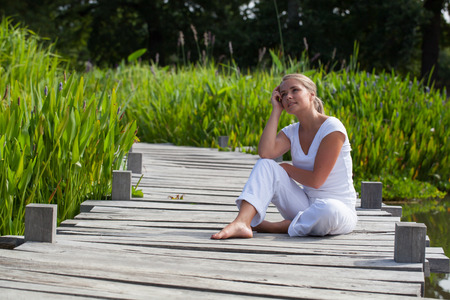 relaxation outside - smiling young woman with bare feet dreaming, sitting on a wooden bridge with water and green background, summer daylight