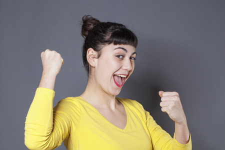 cheeky: success concept - cheeky young woman smiling with a yellow sweater expressing her fun and happiness Stock Photo