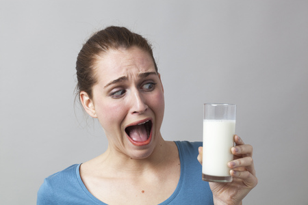 stressed young woman panicking at the idea of drinking a glass of smelly milk or disgusting white beverage