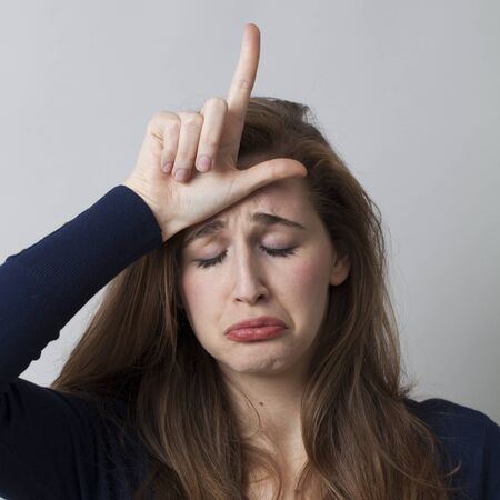 l hand: crying young woman making the L sign on forehead for loser message, cool hand gesture for youth culture