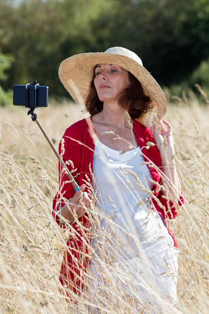 snob: mature selfie concept - snob mature woman posing for selfie with a stick in summer dry meadows wearing a summer hat,natural daylight Stock Photo
