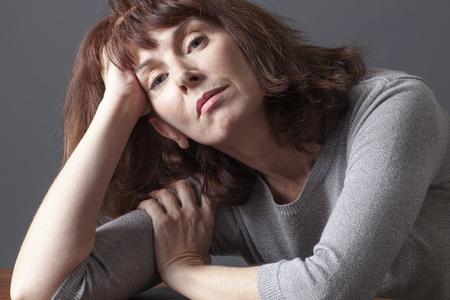 cansancio: renunció mujer madura descansando su rostro en sus manos pensando en sus problemas de envejecimiento o la depresión mayor Foto de archivo