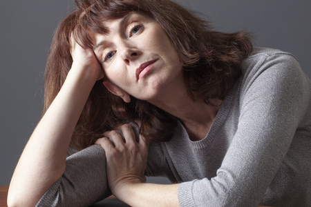 menopause: resigned mature woman resting her face on her hands thinking about her aging problems or senior depression