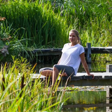 bare feet: relaxation outside - smiling young woman enjoying putting her bare feet in water,sitting on a wooden bridge, green park environment, summer daylight Stock Photo